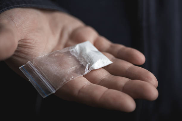 mans hand holding on palm plastic packet with cocaine powder or another drugs. drug dealer proposes to try narcotic concept - narcotico foto e immagini stock