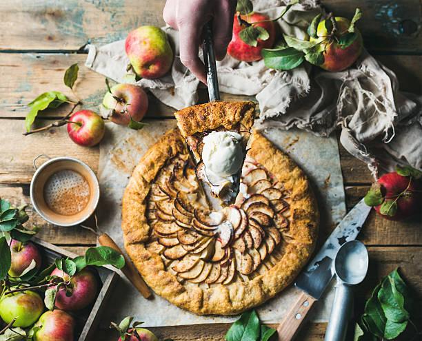 man's hand holding piece of apple crostata pie - crostata stock-fotos und bilder