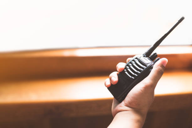 man's hand holding portable walkie-talkie - ham radio stock photos and pictures