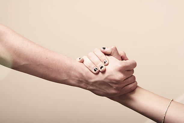 A man's hand holding tight with a woman's hand stock photo