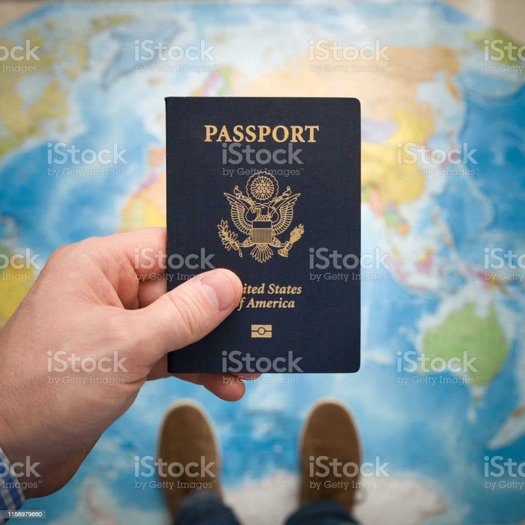 Man\'s hand holding US passport. Map background. Ready for traveling....