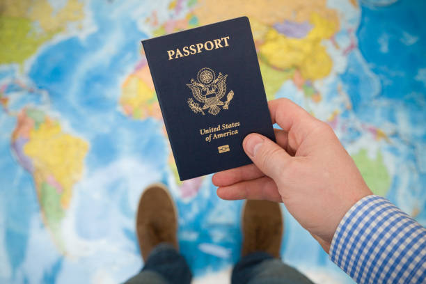 Man's hand holding US passport. Map background. Ready for traveling. Open world. stock photo
