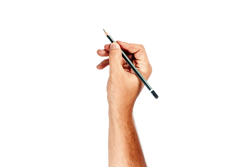 A man's hand holds a black pencil on a white background, isolate.