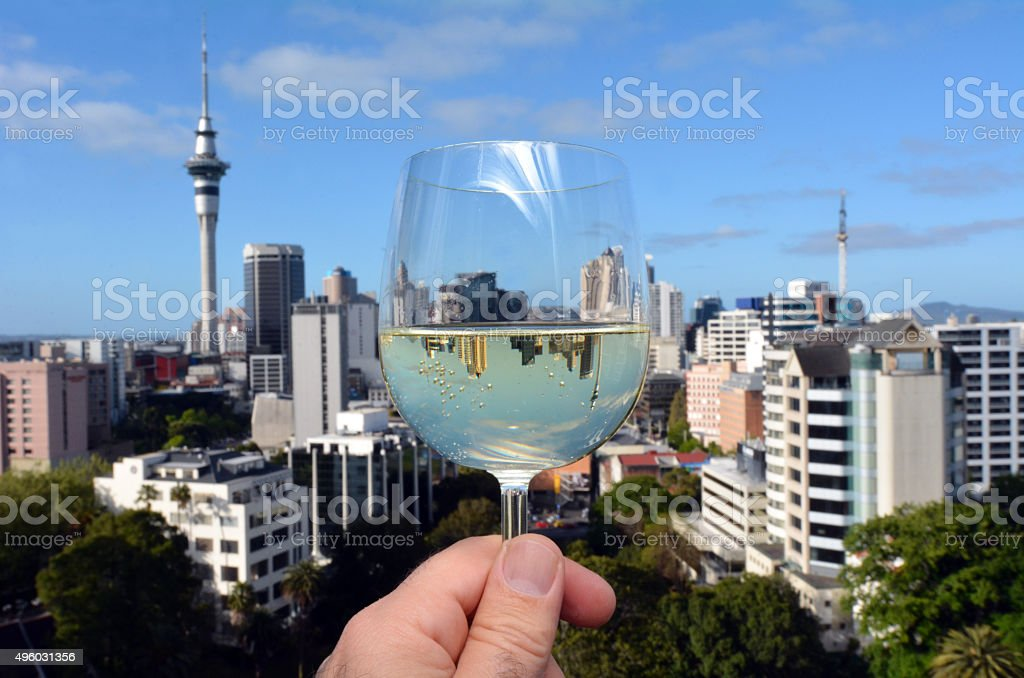 Mans hand holds a white wine glass against Auckland skyline stock photo