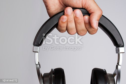A man's hand holds a wireless headset on top of a gray background.