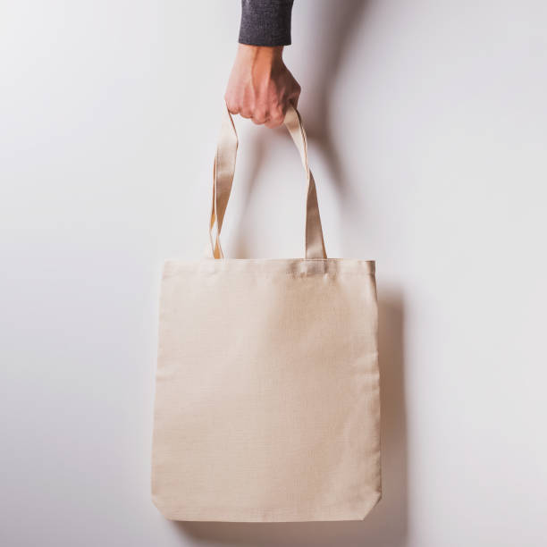 Man's hand holds blank cotton eco tote bag over the white wall stock photo