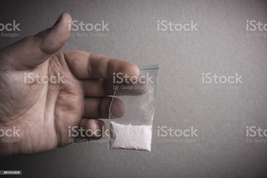 Mans hand holds plastic packet with cocaine powder or another drugs. Drug dealer stock photo