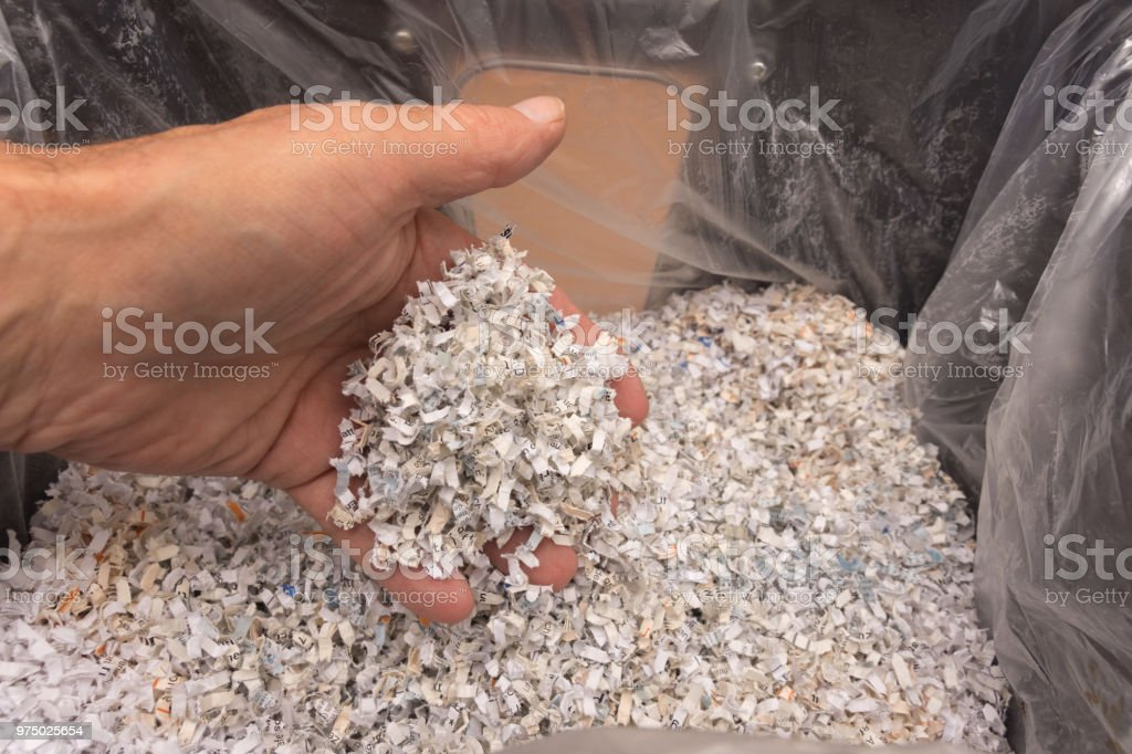 Man's hand holds scraps of paper in his fingers stock photo