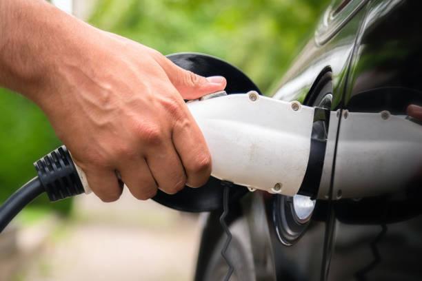 Mans Hand einsetzen Ladegerät Stecker in Elektroauto in grüner Umgebung Hintergrund. Neues Energiefahrzeug, NEV wird mit Strom beladen. Ökologie, moderne Autos – Foto