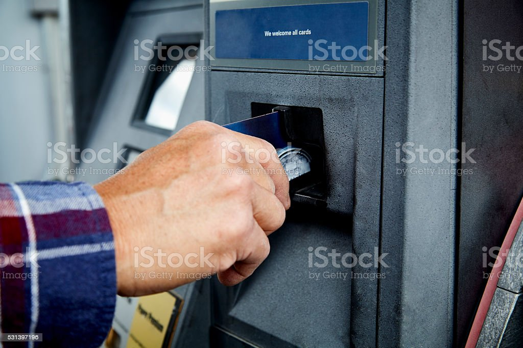 Mans Hand inserting Credit Card at ATM at Gas Pump Man putting credit card in gas pump ATM to pay for gas at a gas station ATM Stock Photo