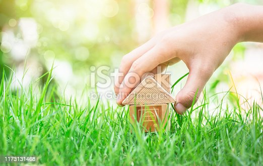 Man's hand is putting the house on the grass. Indicates savings for buying a house. planning savings money of coins to buy a home concept for property, mortgage and real estate investment for a house.