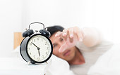 Man's hand is reaching out to alarm clock waking up in early morning