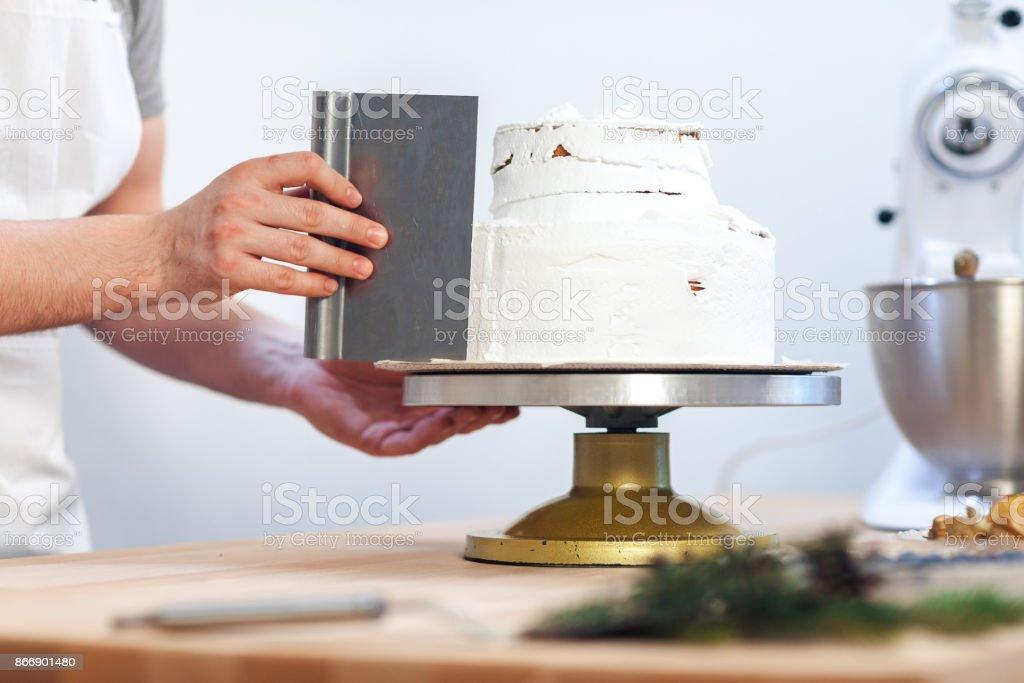 Man's hand levels cream on cake, cake decor on white background, close-up stock photo
