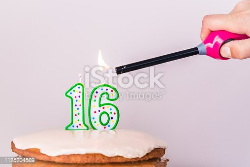 Vegan vanilla layer cake with vanilla frosting and 16th birthday candles being lit my man's hand holding a lighter