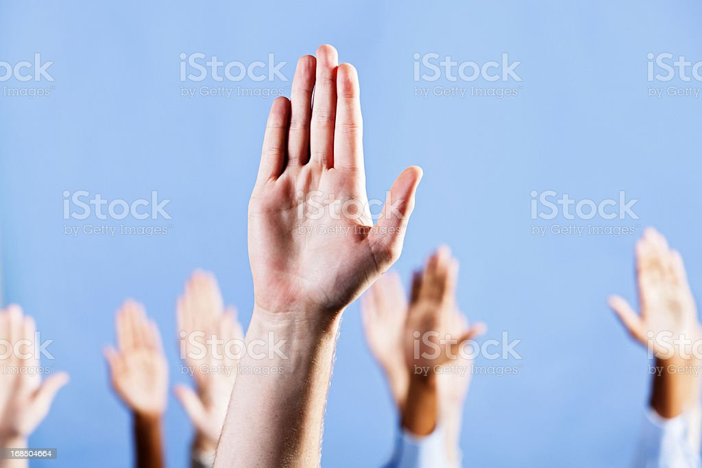 """Man's hand makes """"Stop!"""" gesture with many agreeing in background royalty-free stock photo"""