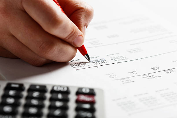 Man's hand marking items on financial document with calculator nearby A person's hand checks a financial document, marking items off with a ballpoint pen, a calculator  standing by. Could be home or office finances being checked so carefully.  accounting ledger stock pictures, royalty-free photos & images