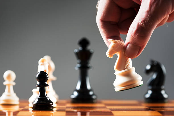 Man's hand moves white knight into position on chessboard stock photo