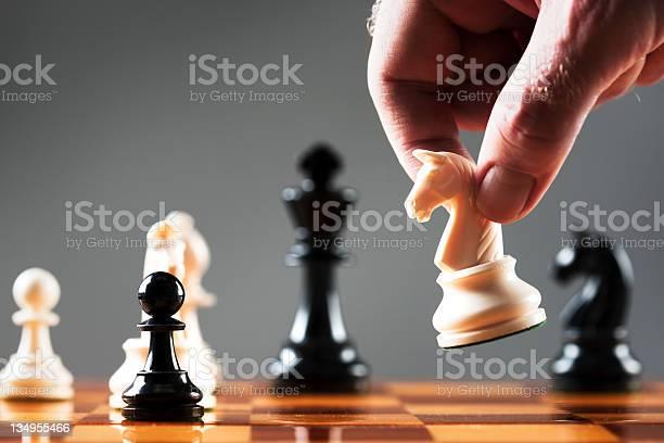 Homem De Mão Se Move Branco Knight Em Posição De Xadrez - Fotografias de stock e mais imagens de Adulto