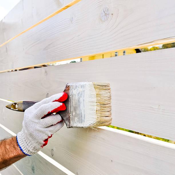 Mann hand Malerei Pinsel auf hölzernen Zaun mit Weiß – Foto