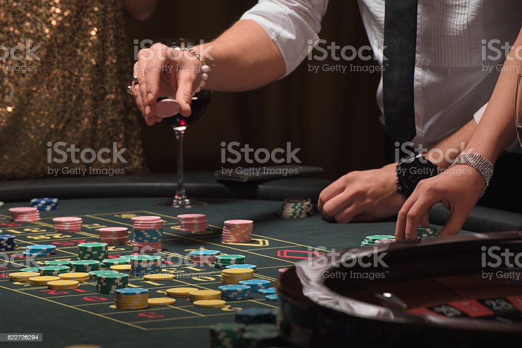 Man's hand placing a bet playing roulette stock photo
