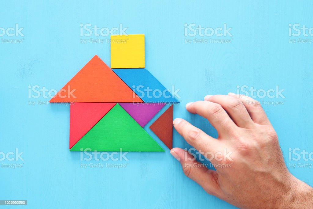 man's hand pointing at house made from tangram puzzle over wooden table stock photo