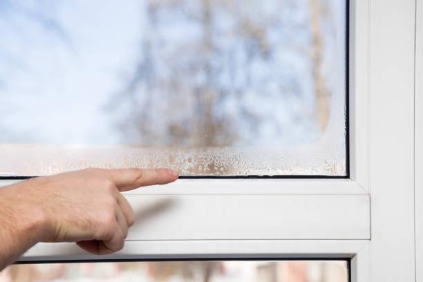 hand des mannes auf die fenster-glas-feuchtigkeit. zimmer lüften problem. - fenster einbauen stock-fotos und bilder