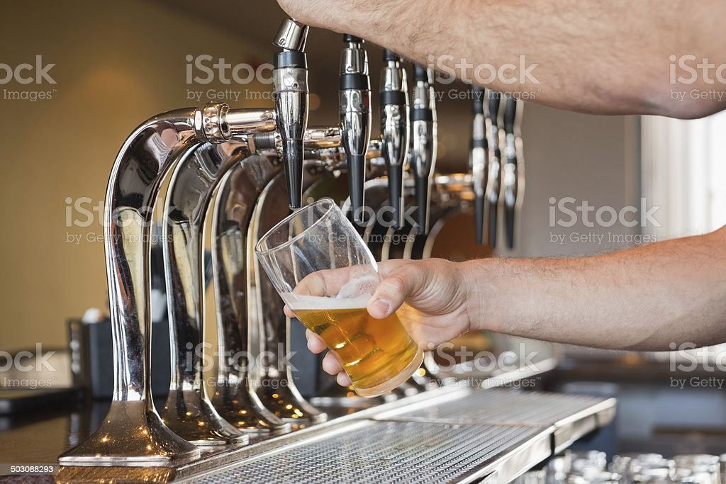 Mans hand pouring beer stock photo