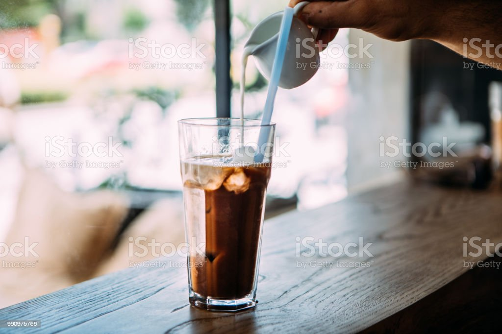 Man\'s hand pouring milk to cold latte coffee cocktail