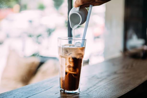 mannes hand gießen milch an kalten latte kaffee cocktail - hausgemachter eiskaffee stock-fotos und bilder
