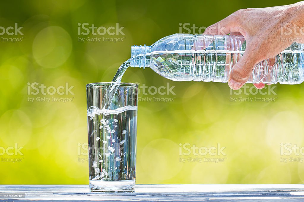 Man\'s hand holding plastic bottle water and pouring water into glass...