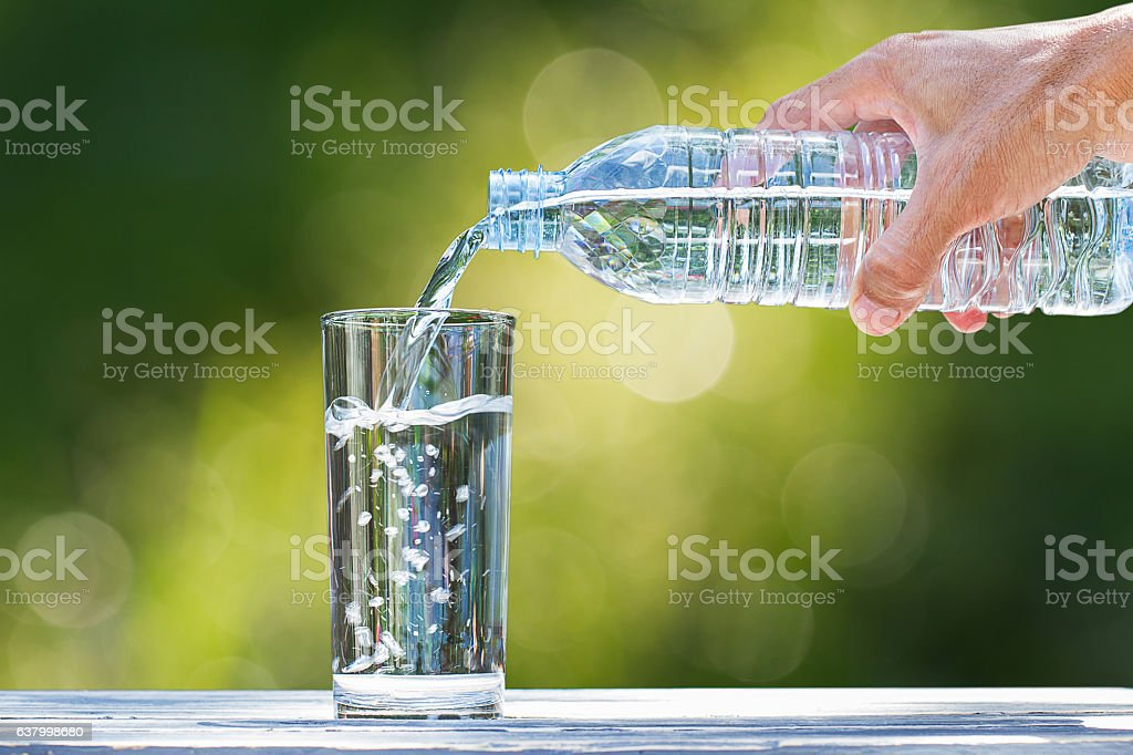 Man's hand pouring water into glass on blurred bokeh background – zdjęcie