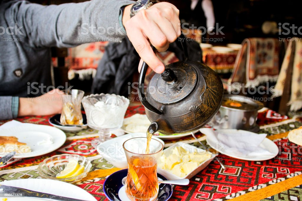 A man's hand pours tea from a metal kettle. Atmosphere of Baku and Eastern traditions. Oriental cuisine stock photo