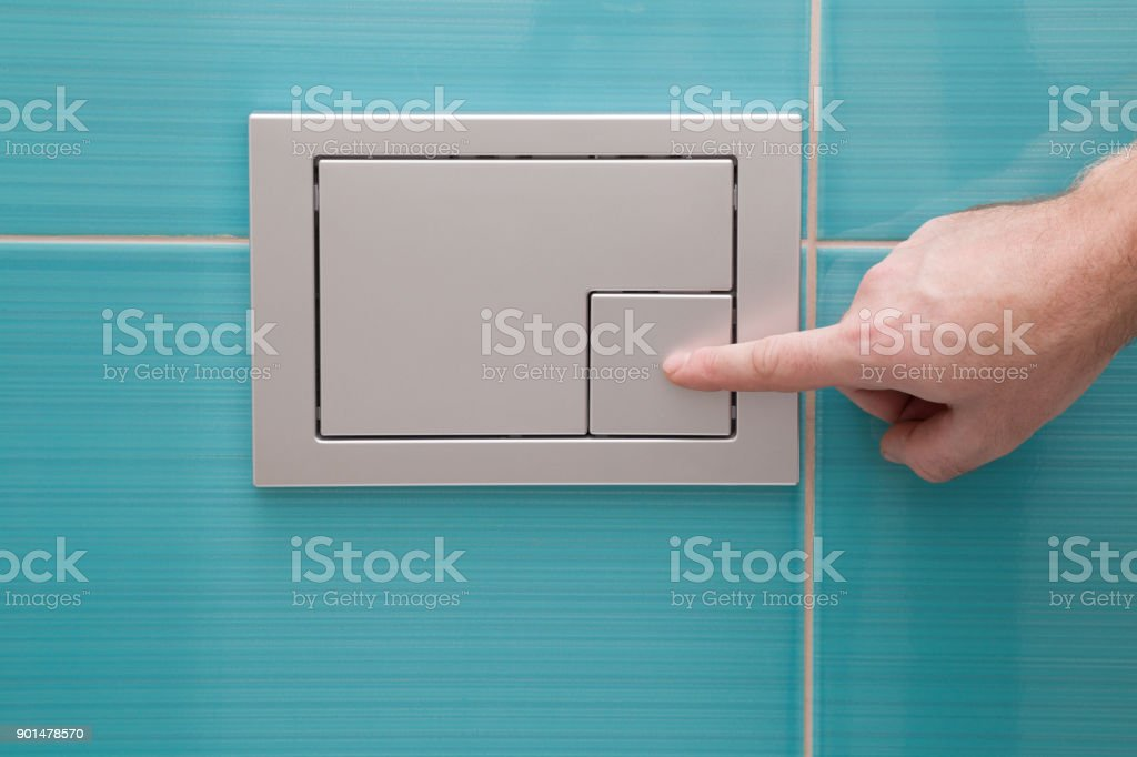 Man's hand pressing a button in the wc. Modern economic toilet flush with two separate buttons at the wall. stock photo