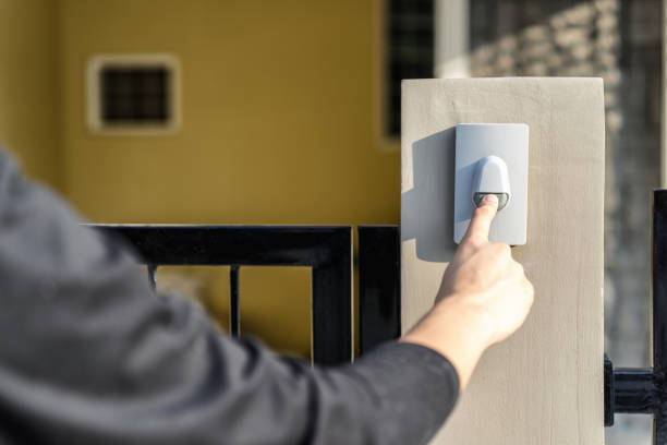 man's hand pressing a doorbell button with sunlight. close up hand and finger visiter ringing buzzer doorbell. guest press bell behind front door home. - squillare foto e immagini stock