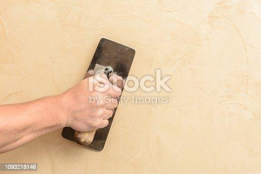 Man's hand put a Venetian cloth on the wall 2018