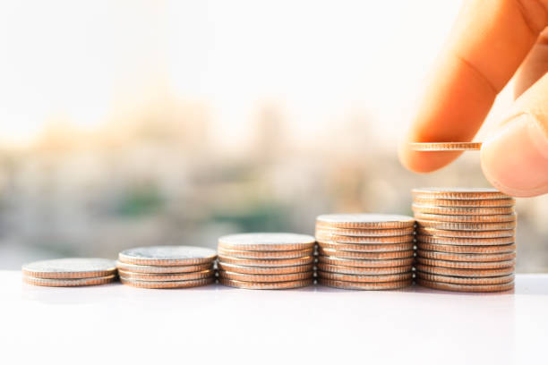 Man's hand put money coins to stack of coins. Money, Financial, Business Growth concept. stock photo