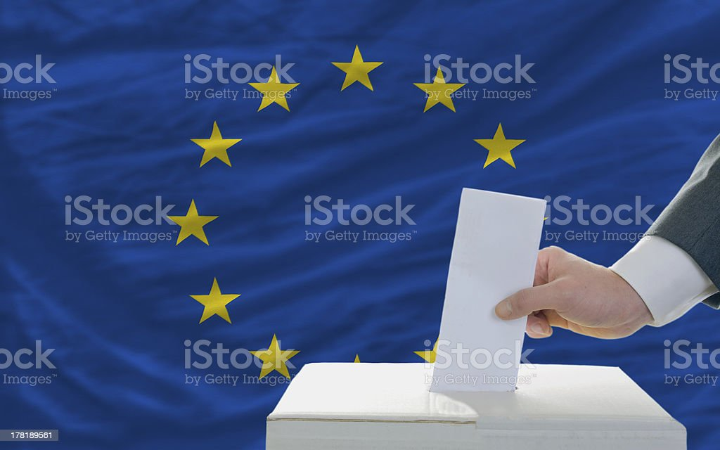 Man's hand putting ballot in box in EU election royalty-free stock photo