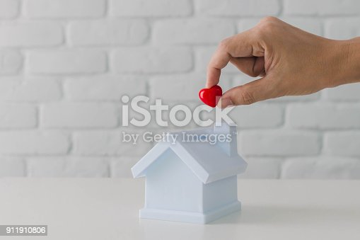 Man's hand putting red heart in to house piggy bank metaphor saving love for lover or family in every day.Concept of happy relationship at home.