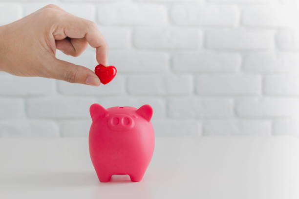 Man's hand putting red heart in to piggy bank metaphor saving love for lover or family in every day.Concept of happy relationship. stock photo