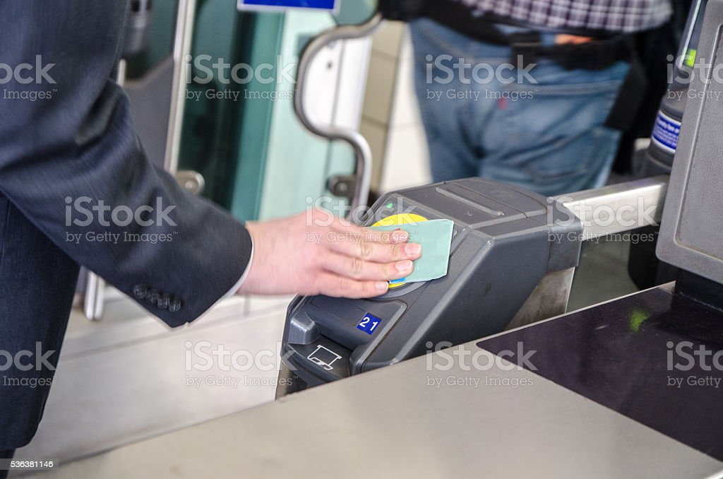 Man's hand putting subway card on detector to open entrance stock photo