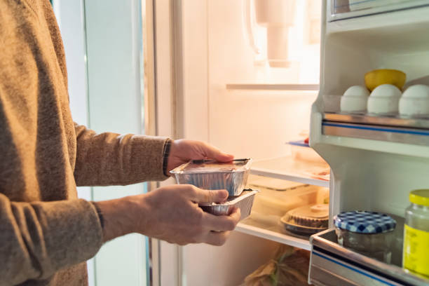 Man's hand putting takeout meal in refrigerator. stock photo