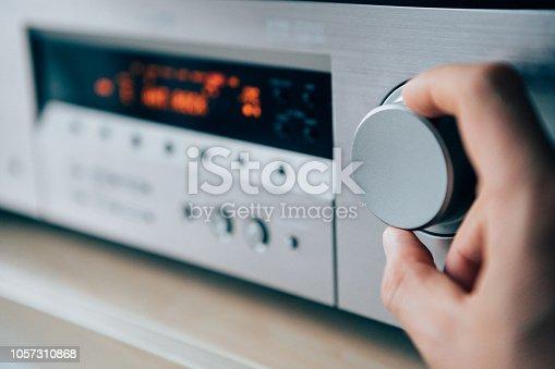 istock Mans hand rotating the Amplifier Volume regulator Adjusting the loudness 1057310868