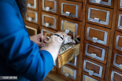 668340340istockphoto Man's hand searching for files into library or archive 1026135764