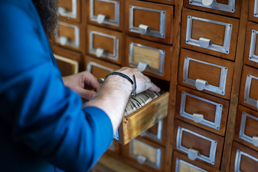 668340340 istock photo Man's hand searching for files into library or archive 1026135764