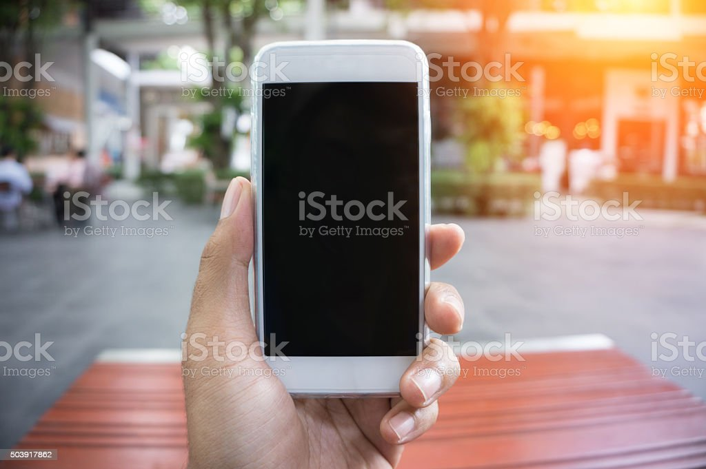 Man's hand shows mobile smartphone in vertical position stock photo