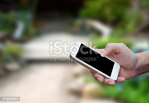 534217898istockphoto Man's hand shows mobile smartphone in vertical position 516360824