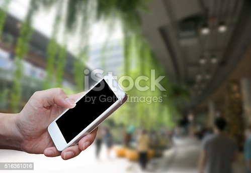 534217898istockphoto Man's hand shows mobile smartphone in vertical position 516361016
