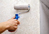 istock man's hand smoothing the wallpaper with a roller closeup 695644924