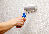 istock man's hand smoothing the wallpaper with a roller closeup 695645580