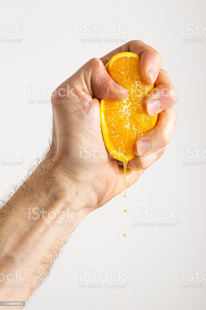 Man's Hand Squeezing Half an Orange stock photo